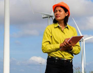 bild på kvinna i skyddshjälm som står framför några vindkraftverk df0b731374988